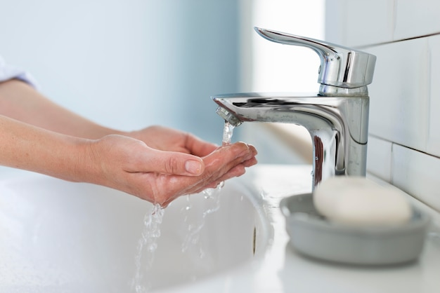 Вид сбоку лица, моющего руки водой