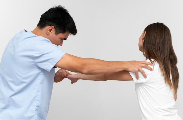 Физиотерапевт, делающий упражнения на плечо с женщиной, вид сбоку