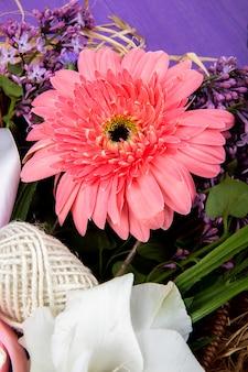 Вид сбоку розового цвета цветка герберы с сиренью на фиолетовом фоне