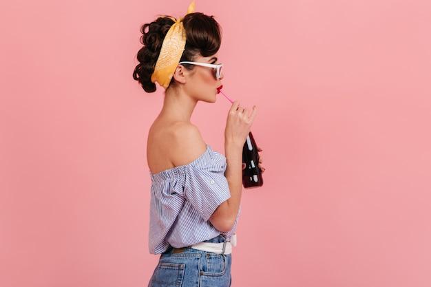 ソーダを飲むピンナップブルネットの女の子の側面図。ピンクの背景に分離されたヴィンテージの衣装でスタイリッシュな若い女性のスタジオショット。