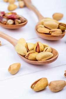 Вид сбоку фисташковых орехов на деревянной ложкой на белом фоне