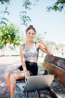 Вид сбоку довольной брюнетки, сидящей на скамейке в парке и использующей портативный компьютер