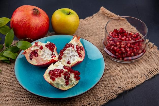 Вид сбоку дольки граната на синей тарелке с яблоком на бежевой салфетке