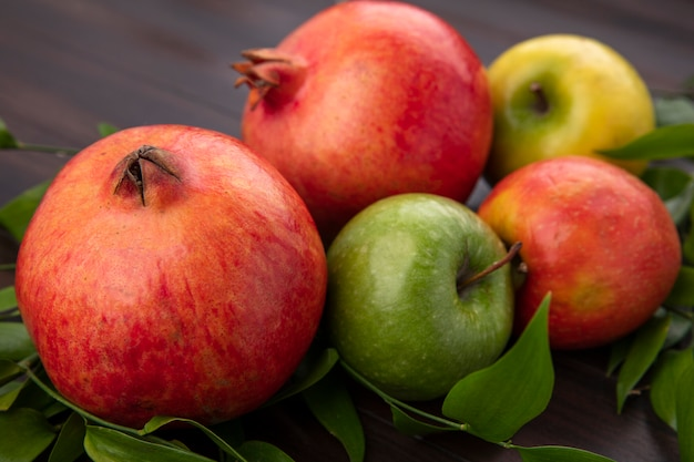 Вид сбоку граната с цветными яблоками и ветвями листьев на деревянной поверхности
