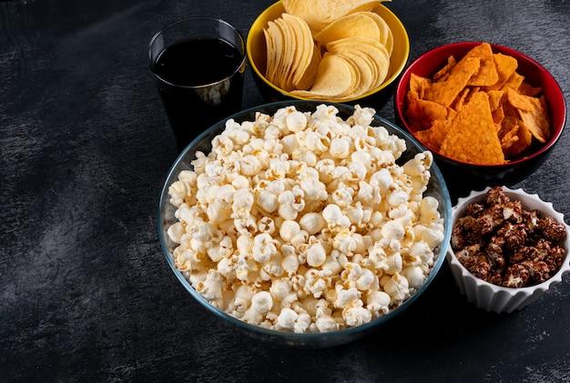 Вид сбоку попкорна и чипсов в мисках на черном горизонтальном