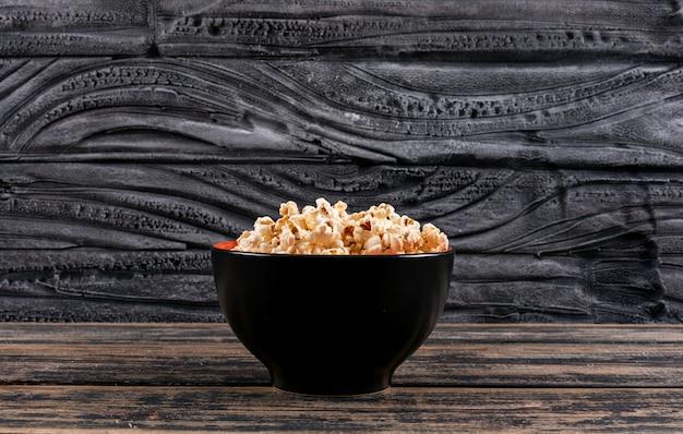 暗い木製のテーブルの水平方向のボウルにポップコーンの側面図