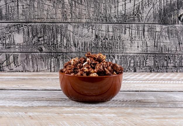 ボウルにポップコーンの横の白い木製のテーブルの側面図