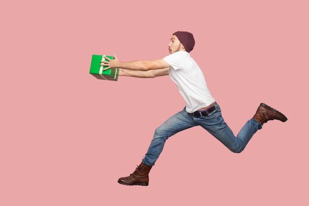 흰 셔츠와 캐주얼 모자 점프, 달리기, 배달 녹색 선물로 서둘러 수염 난 젊은 힙스터 남자의 초상화의 측면 보기. 실내, 절연, 스튜디오 촬영, 분홍색 배경
