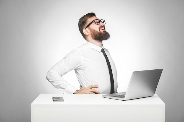 Вид сбоку портрета нездорового расстроенного молодого менеджера в белой рубашке и черном галстуке сидит в офисе и сильно болит спина или почки. закрытый, студийный снимок, изолированный, серый фон