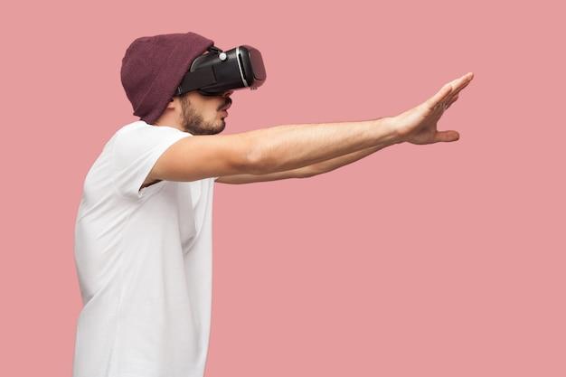 흰 셔츠와 평상복 모자를 쓴 수염난 젊은 힙스터 남자가 팔을 들고 비디오 게임을 하는 vr을 입고 궁금해하는 초상화의 측면 보기. 실내, 절연, 스튜디오 촬영, 분홍색 배경