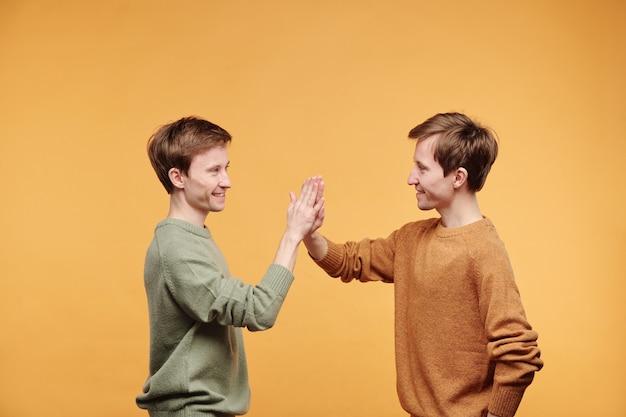 オレンジ色の背景に立って5を与えるカジュアルセーターのポジティブハンサムな若い双子の側面図