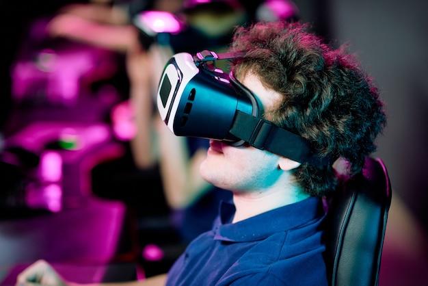 Вид сбоку на позитивного молодого кудрявого геймера, играющего в видеоигру в очках виртуальной реальности