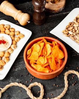 Вид сбоку картофельные чипсы с паприкой в глиняной миске