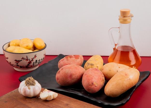 Вид сбоку картофеля в тарелку и миску с топленым маслом и чесноком на разделочную доску на поверхности бордо и белом фоне