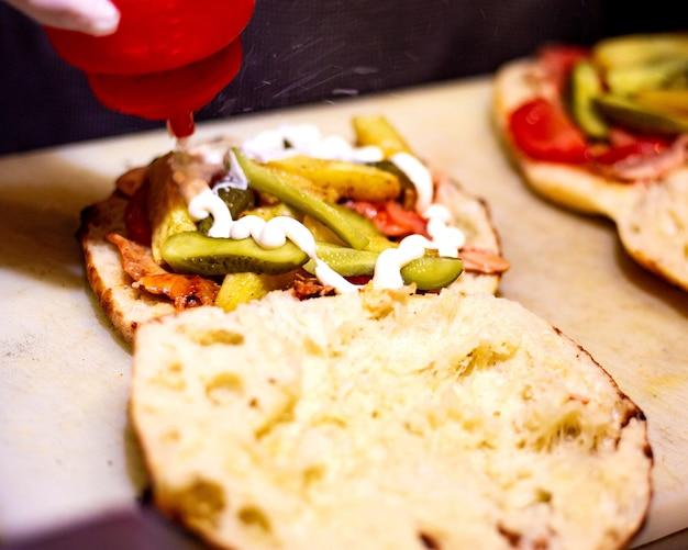 Вид сбоку наливания майонеза в куриный донер в хлеб с солеными огурцами