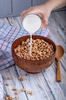 Вид сбоку наливая молоко на воздушный сладкий рис деревенском