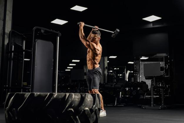 쇠 망치로 거대한 타이어를 치는 강력한 근육질 남자의 측면보기.