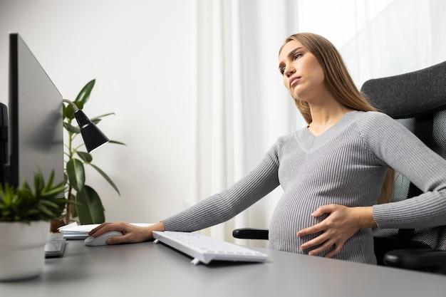Вид сбоку беременной бизнес-леди за столом, держащей ее живот
