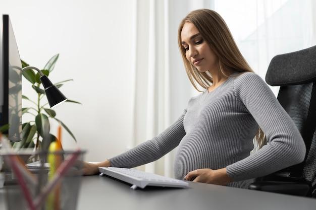 Беременная бизнесвумен в офисе, вид сбоку