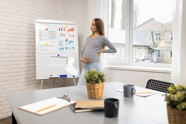 オフィスでホワイトボードと妊娠中の実業家の側面図