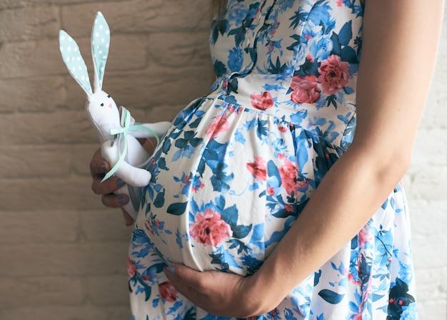 Вид сбоку беременной матери, держащей игрушечного кролика возле живота