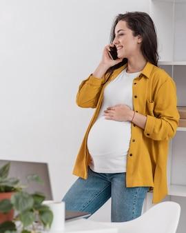 Беременная женщина дома разговаривает по телефону, вид сбоку