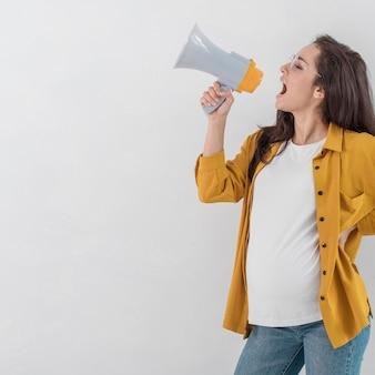 Беременная женщина кричит в мегафон, вид сбоку