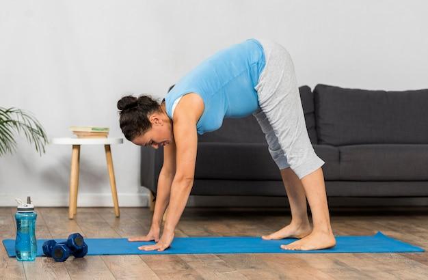 マットの上で自宅でトレーニングしている妊婦の側面図