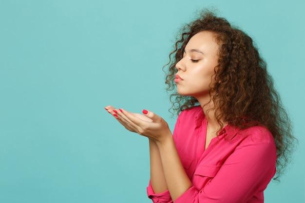 스튜디오의 파란색 청록색 벽 배경에 격리된 손에 무언가를 들고 분홍색 캐주얼 옷을 입은 예쁜 아프리카 소녀의 측면. 사람들은 진심 어린 감정, 라이프 스타일 개념입니다. 복사 공간을 비웃습니다.