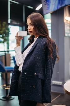 カフェに立って、目をそらしながら白いコーヒーを持っているかなり穏やかなブルネットの側面図。