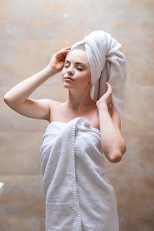 Вид сбоку красивой женщины с полотенцем на голове и в халате позирует. портрет женщины с голым плечом, наслаждаясь временем после свежего душа. красота, концепция ухода за кожей.