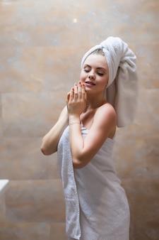 머리와 목욕 가운 포즈에 수건으로 예쁜 여성의 측면보기. 신선한 샤워 후 시간을 즐기는 벌 거 벗은 어깨를 가진 여자의 초상화. 뷰티, 스킨 케어 개념.