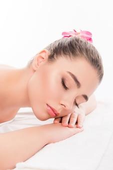 Красивая девушка, лежа в сауне с закрытыми глазами, вид сбоку