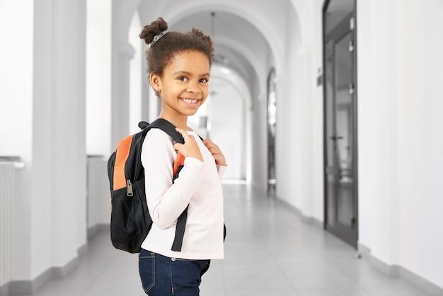 Вид сбоку довольно маленькой африканской школьницы, идущей в школе на перемене
