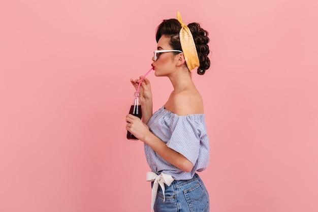 검은 머리와 예쁜 핀 업 여자의 측면보기. 음료를 마시는 복고풍 복장에 귀여운 여자의 스튜디오 샷.