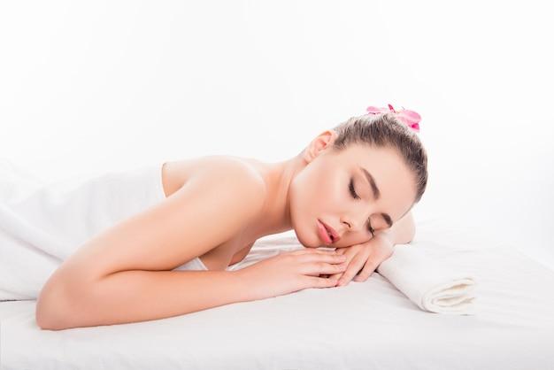 Вид сбоку довольно молодой женщины, лежащей в спа-салоне с закрытыми глазами
