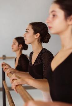 Вид сбоку на репетиции профессиональных балерин в купальниках
