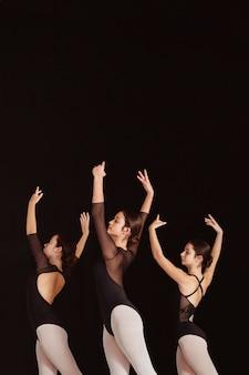 Вид сбоку профессиональных артистов балета в трико с копией пространства