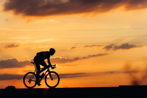 屋外で黒い自転車でスポーツ活動をしているプロのサイクリストの側面図