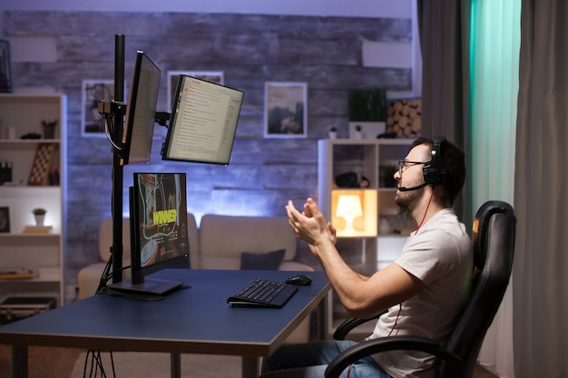 Вид сбоку на профессионального стрелка-геймера, хлопающего в ладоши после победы на важном онлайн-соревновании.