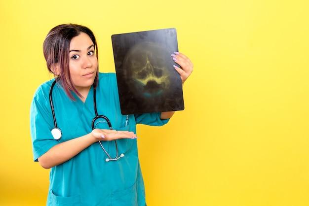 방사선 전문의의 측면보기 방사선 전문의가 환자 머리의 x- 선 영상에 대해 이야기합니다.
