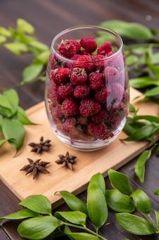 Вид сбоку малины в стакане на разделочной доске с ветвями листьев на деревянной поверхности