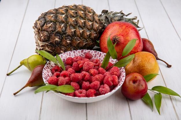 Вид сбоку малины в миске с гранатом, ананасом, персиком, сливой и яблоком на белом
