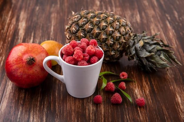 Вид сбоку малины в чашке с ананасом, гранатом, персиком с листьями вокруг на дереве