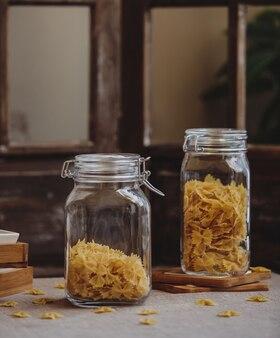 Вид сбоку сырой фарфалле макароны в стеклянных банках на деревянном столе