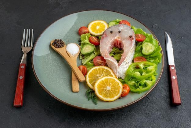 회색 접시에 생선과 신선한 다진 야채 레몬 슬라이스 향신료의 측면보기와 칼 붙이 검은 고민 표면에 설정