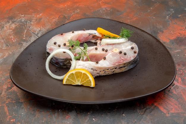 혼합 색상 표면에 검은 접시에 원시 물고기와 고추 레몬 슬라이스 양파의 측면보기
