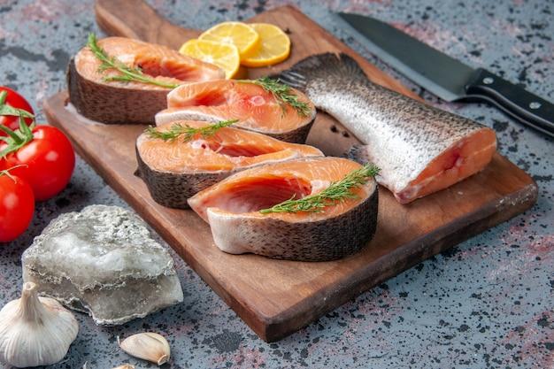 Вид сбоку сырых рыб, ломтиков лимона, зелени, перца на деревянной разделочной доске и ножа для овощей на столе сине-черных цветов