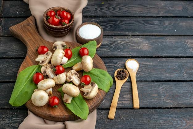 黒の背景に木の板タオルで生の新鮮なキノコとトマトのスパイスの側面図