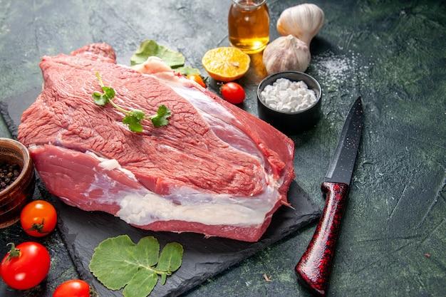 まな板ナイフトマトの生の新鮮な赤身の肉と緑の側面図緑黒ミックス色の背景にレモンオイルをカット